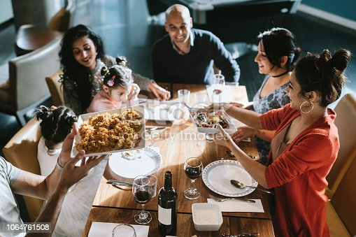 A group of adult friends and family of Indian ethnicity sit a table with a spread of delicious traditional food.  They pass hot serving dishes of food to one another. Shot in Bellevue, Washington, United States.