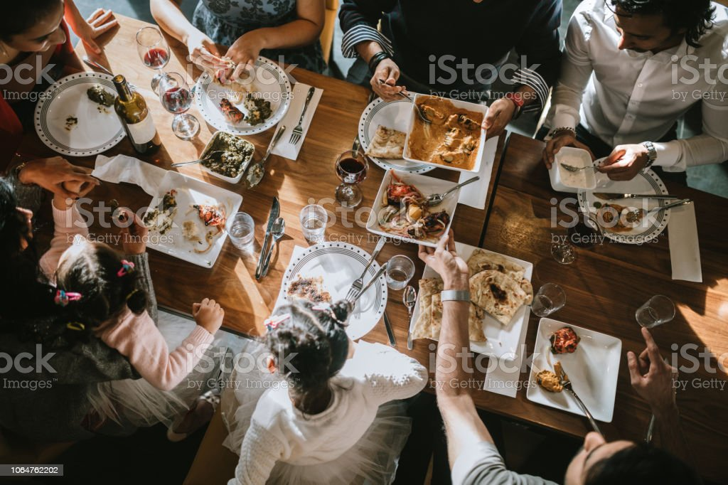 Indian Friends and Family Share Traditional Meal Together stock photo