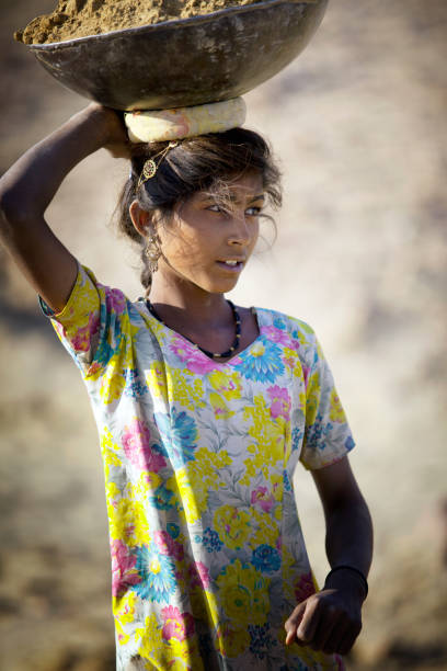 Indian girl carrying a basket of sand on his head shot in the state of Rajasthan in India in November 2009 stock photo