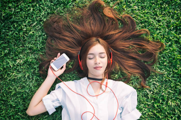 India chica escuchando música con auriculares de teléfono inteligente de streaming en verano en un prado. - foto de stock