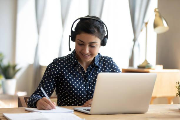 studentessa indiana indossare auricolare studio insegnante online scrivere note - internet foto e immagini stock