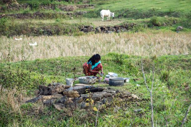 indische mädchen beim abwasch am brunnen auf dem lande - dorfkind momente stock-fotos und bilder