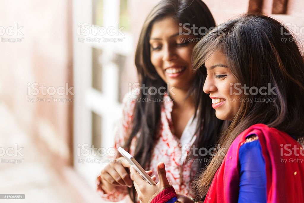 indian girls using smartphone stock photo