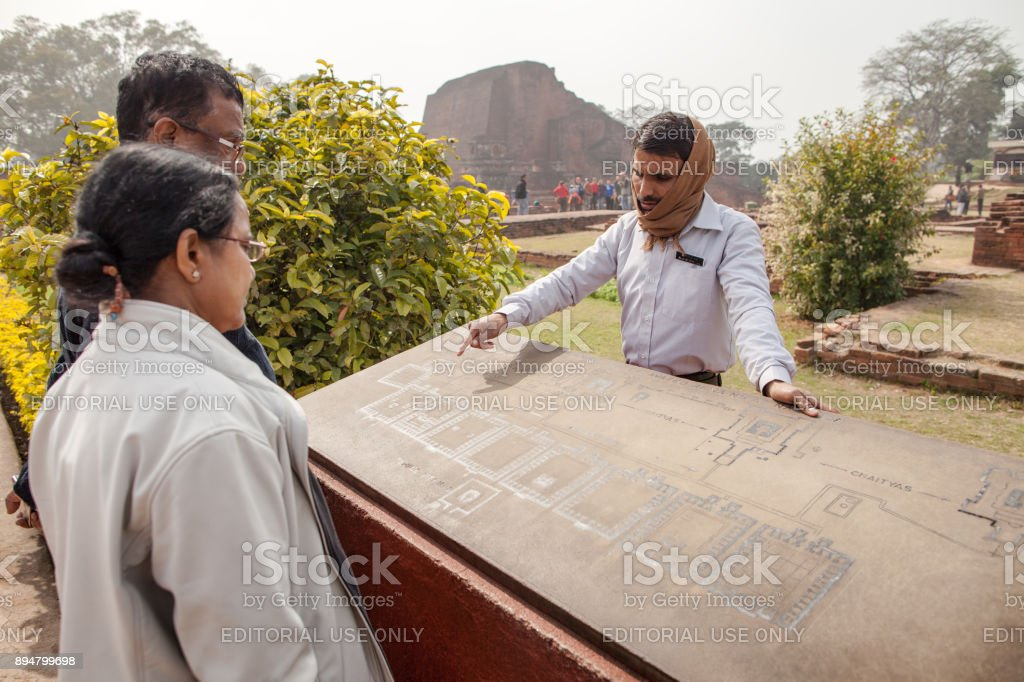Indian guide shows to tourists an objects on a map. stock photo