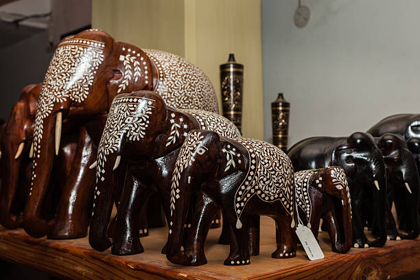 Indian handicraft - inlaid rosewood elephants for sale Indian handicraft inlaid rosewood elephants for sale on a shelf.  The inlay work  creates  patterns on the carved elephants, in line with decorations used on domesticated elephants for Indian temple or other ceremonies.  These elephants are created by hundreds of craftsmen in different areas of the Country.  There is no copyright or trade mark protection linked to these creations; infact many craftsmen will not even be able to recognise their own work.  Tourists to India buy them as souvenirs, by the thousands. Focus on elephant in the foreground; shallow depth of field.   Horizontal format. No people. chandra dhas, stock pictures, royalty-free photos & images