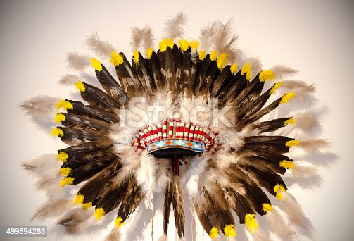 An Indian headdress with eagle featheres and on a white background.