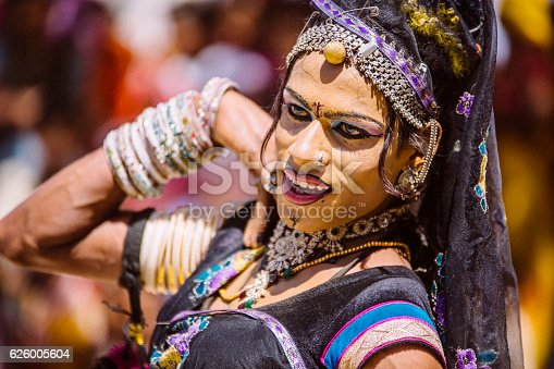 In Sabalpura, India, an Indian Hijra (hermaphrodite) dressed up for a dancing performance. Unrecognizable villagers, in the background, all present to watch the show.