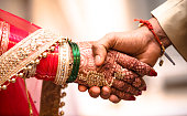 istock Indian Hindu Couple holding each other hands during their marriage symbolising love and affection. Hands of bride is decorated beautifully by indian mehndi art alongwith jewellery and colorful bangles 1141906552