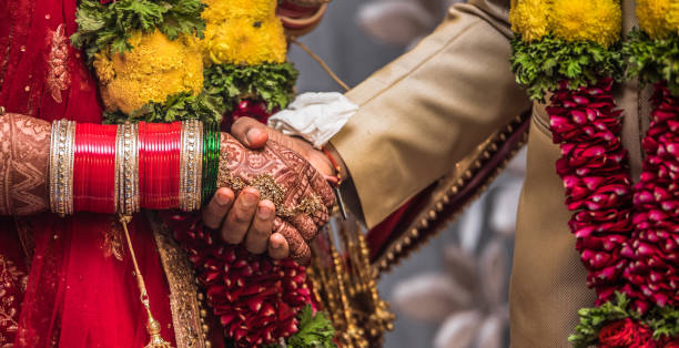 indian hindu couple wearing traditional indian dress and floral garland, holding each other hands during their marriage promising blissful life. beautiful henna mehndi art and bangles on birde hands - induismo foto e immagini stock