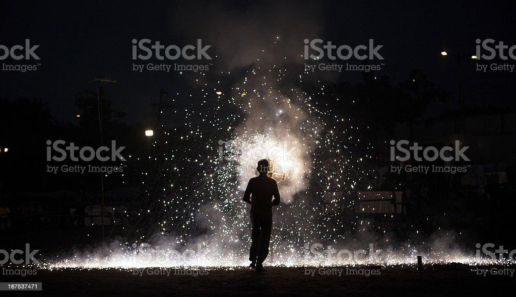 Indian Hindu devotee looks on as fire crackers burn royalty-free stock photo