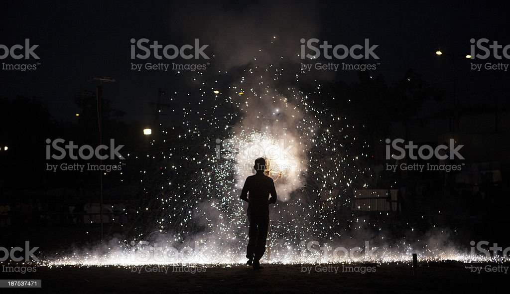 Indian Hindu devotee looks on as fire crackers burn stock photo