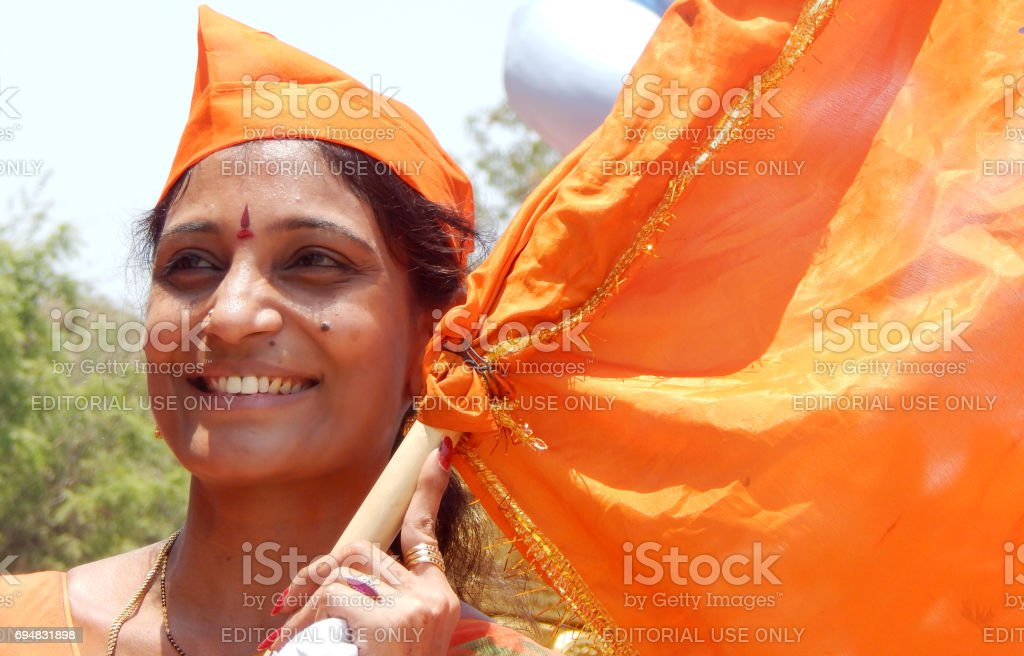Indian Hindu woman waving saffron flag a tradition during sri ram navami festival celebrations,Hyderabad,India stock photo