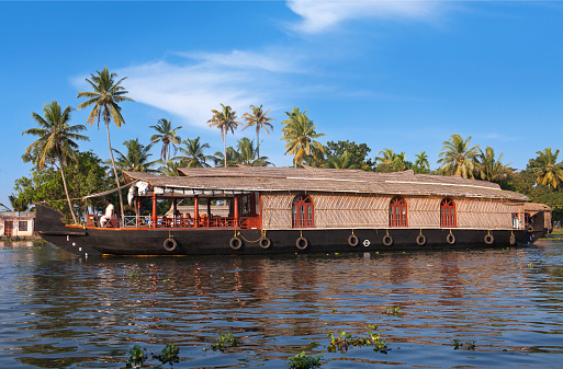 Alleppey, India - November 7, 2016: Tourists on houseboat floating in backwaters in Kerala state, South India