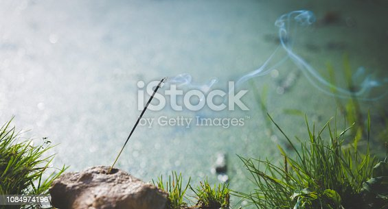 istock Indian incense lit smoking stick against the background of water. 1084974196