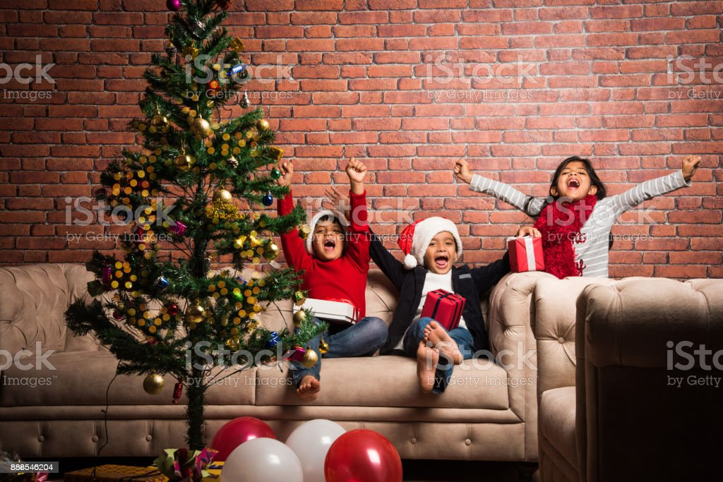 Indian Kids Celebrating Christmas With Decorated Tree And Gifts
