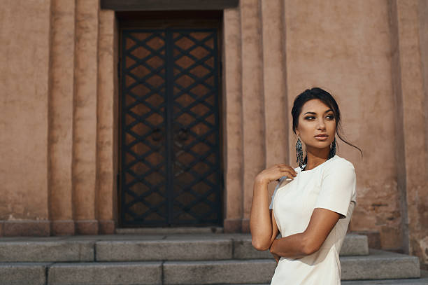 indian lady in dress against ancient building with thoughtful look stock photo