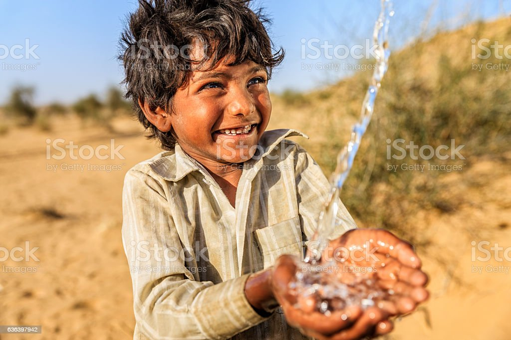Indian little boy drinking fresh water, desert village, Rajasthan, India stock photo