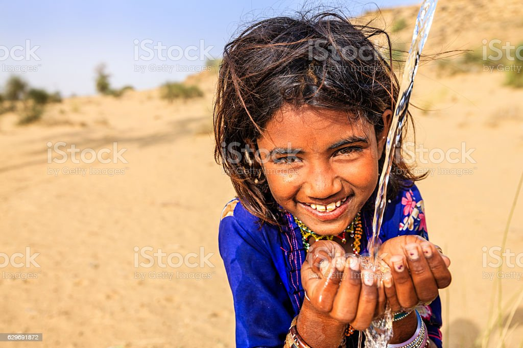Indian little girl drinking fresh water, desert village, Rajasthan, India stock photo