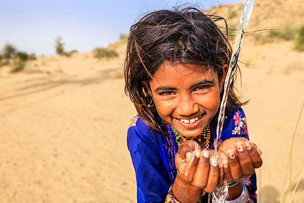 Indian little girl drinking fresh water, desert village, Rajasthan, India Indian little girl is drinking fresh water, desert village, Thar Desert, Rajasthan, India. Potable water is very precious on the desert - Rajasthani women and children often walk long distances through the desert to bring back jugs of water that they carry on their heads.  developing countries stock pictures, royalty-free photos & images