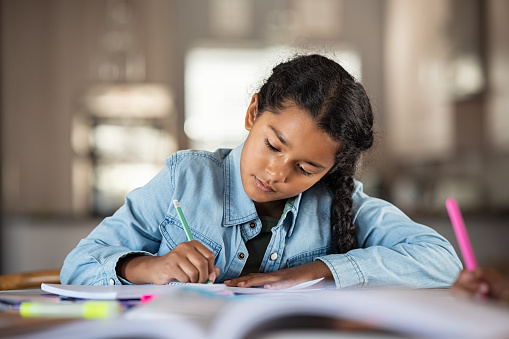 Middle eastern girl doing homework writing and reading at home. Concentrated beautiful indian female child writing in her notebook. Focused latin schoolgirl studying and preparing for exams.