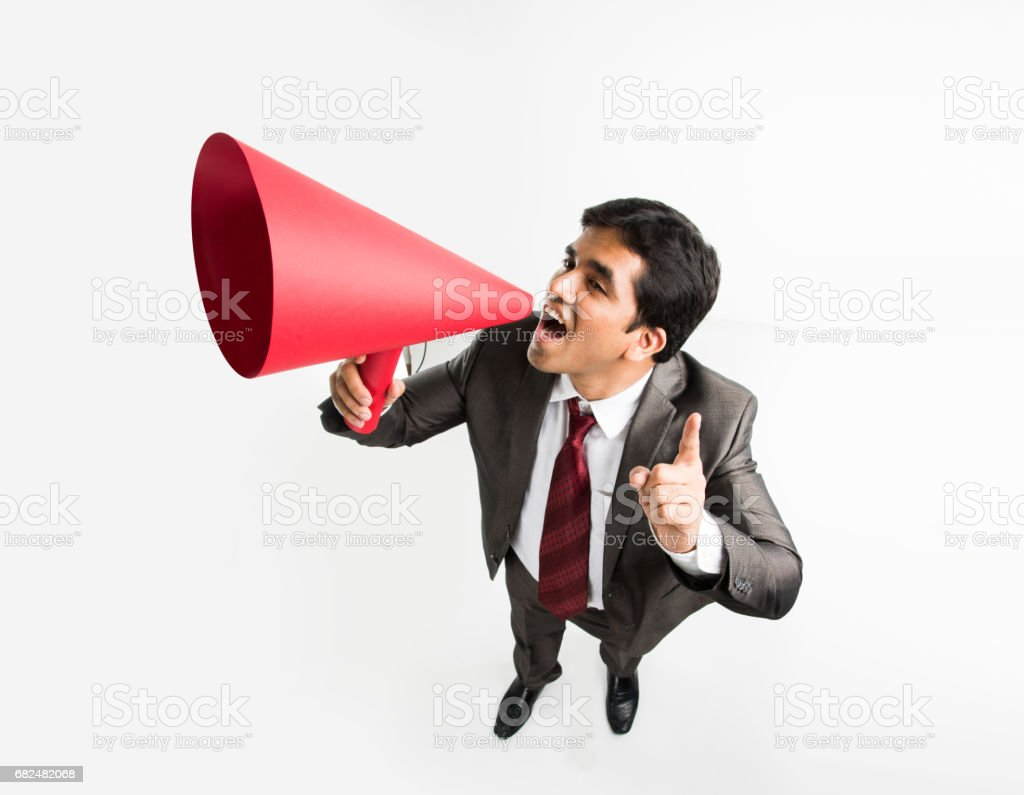 indian male businessman announcing or spreading news using red speaker or mega mic made up of paper, isolated over white background royalty-free stock photo