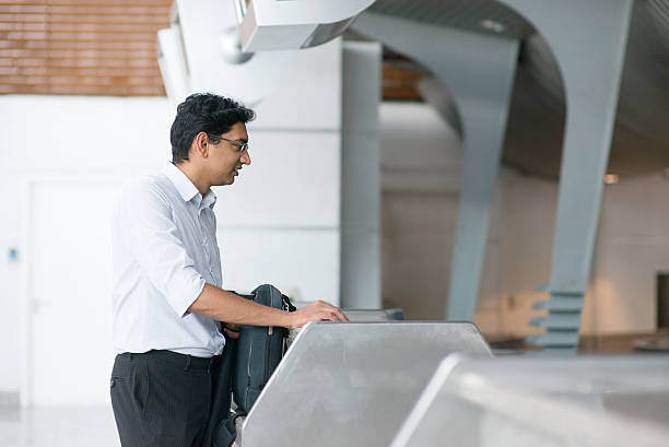 Indian man at airport check in counter Asian Indian businessman standing by airport check in counter pasport malaysia stock pictures, royalty-free photos & images