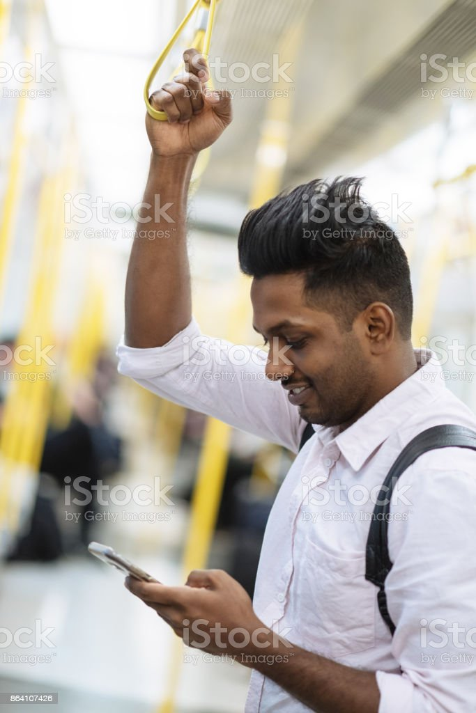 Indian man commuting to work and using phone royalty-free stock photo