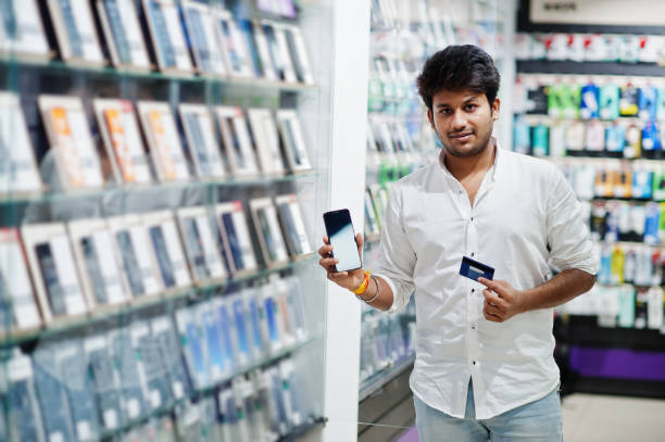 Indian man customer buyer at mobile phone store. South asian peoples and technologies concept. Cellphone shop. stock photo