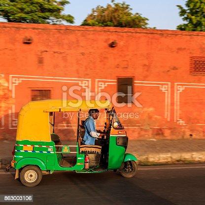 Indian man drives auto rickshaw (tuk-tuk) on streets of Rajasthan, India.