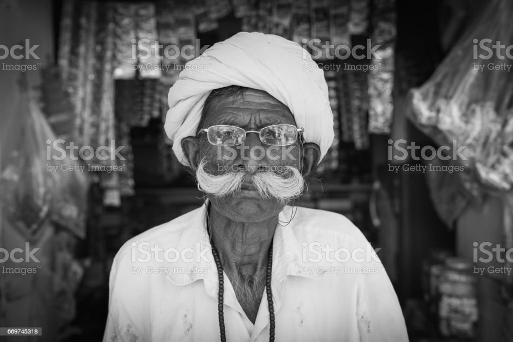 Senior indian man sitting in front of his small store in the streets...