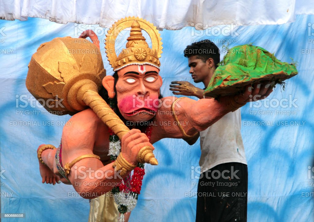 Indian man making a sculpture of Hindu god Hanuman  during Hanuman Jayanti, an important festival of Hindus stock photo