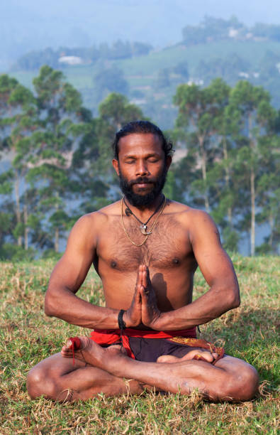 Indian man meditating in lotus yoga pose on green grass Healthy life exercise concept - sporty fit Indian man meditating in lotus yoga pose on green grass in Kerala, South India yogi stock pictures, royalty-free photos & images