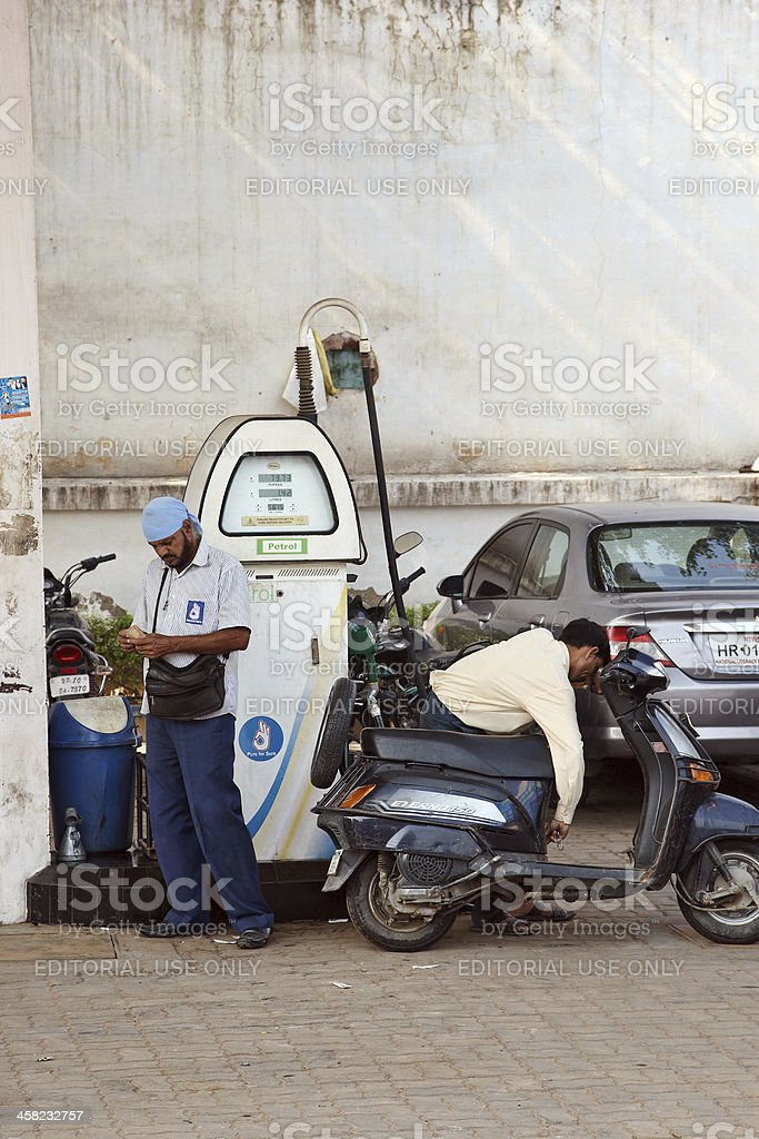 Indian man on scooter and pump attendant at gas station royalty-free stock photo