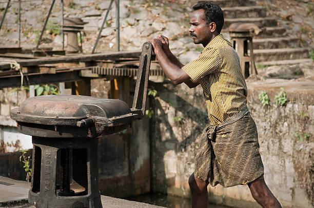 Indian man opening sluice gates. stock photo