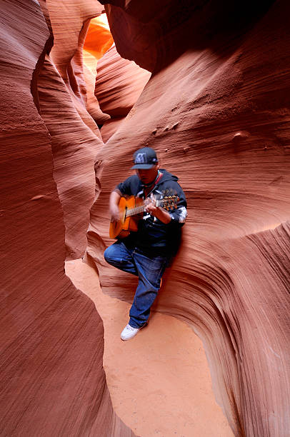 indian man playing guitar in lower antelope canyon, arizona, usa - lower antelope canyon stock photos and pictures