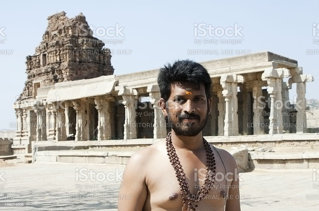 Indian man poses for photograph in front of temple royalty-free stock photo
