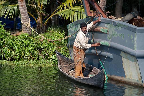 Indian man repairing the boat. stock photo