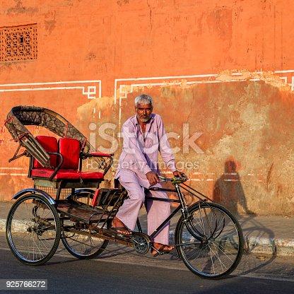 Indian man rides cycle rickshaw on streets of Rajasthan, India.