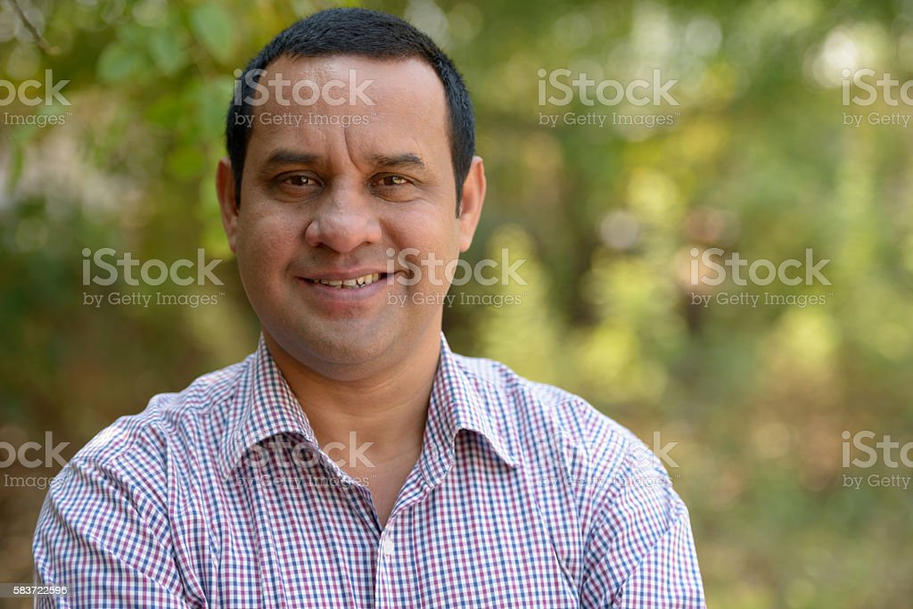 Indian man smiling outdoors stock photo