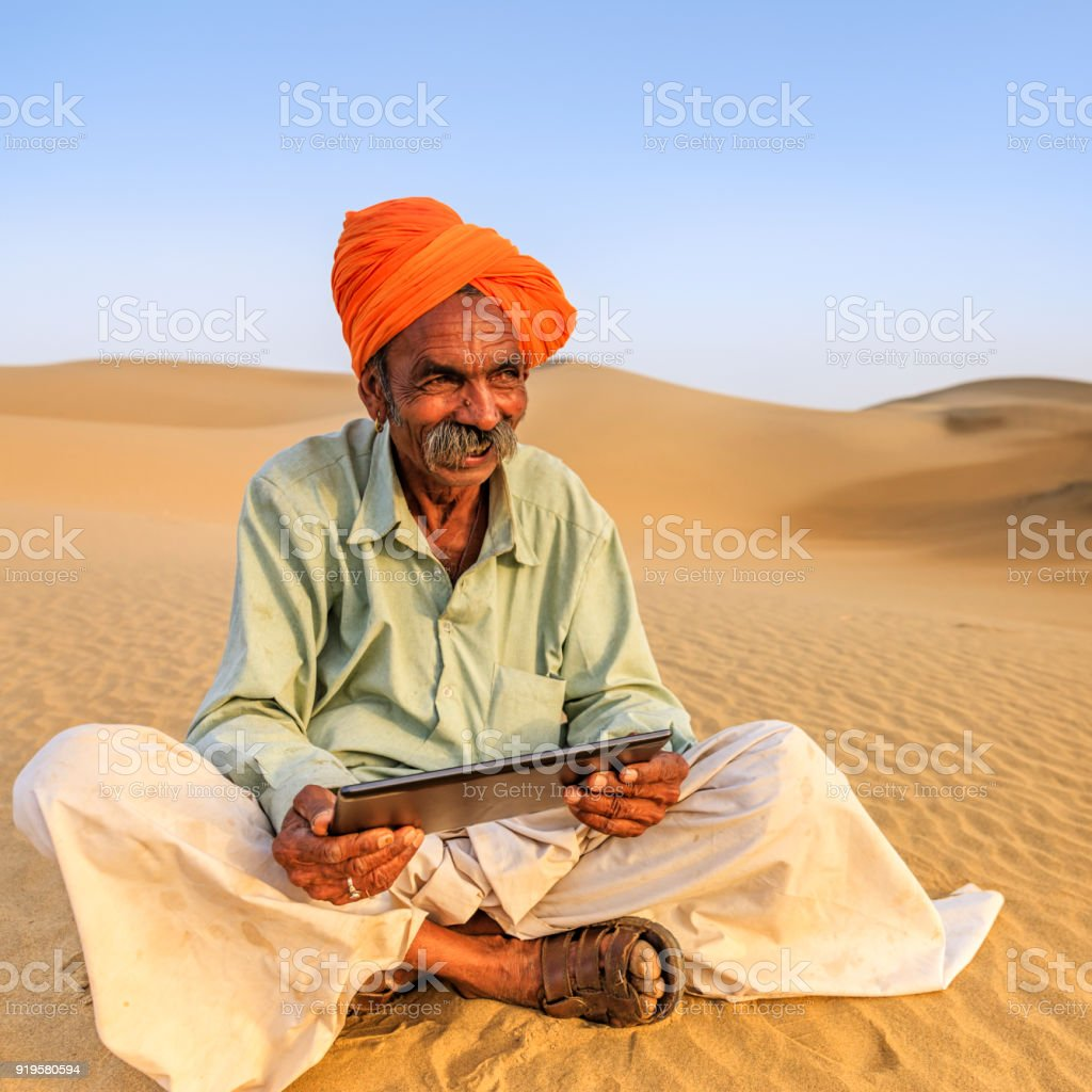 Indian man using a digital tablet, desert village, India stock photo