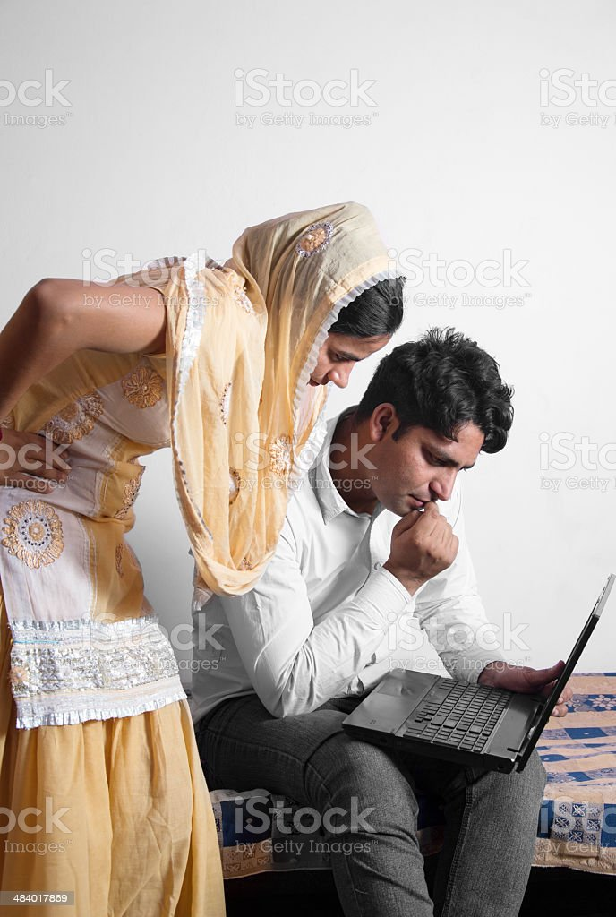 Indian Man using laptop with his wife stock photo
