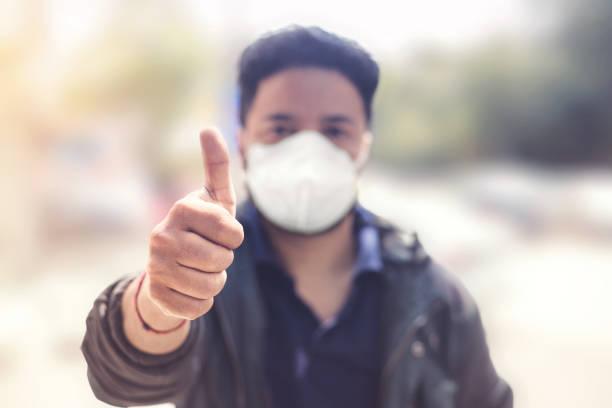 Indischer Mann trägt Maske und zeigt Daumen hoch zum Schutz vor Viren, Staub, Verschmutzung und Smog. – Foto
