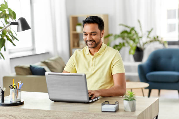 indian man with laptop working at home office stock photo