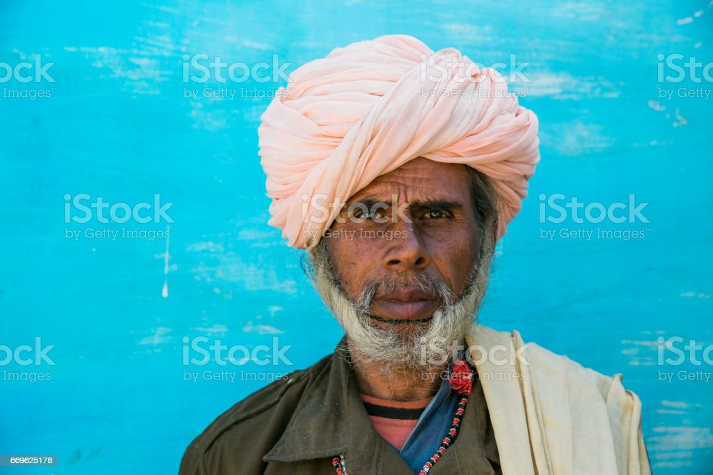 Middle-Aged Adult Indian Man with rose colored turban in front of...