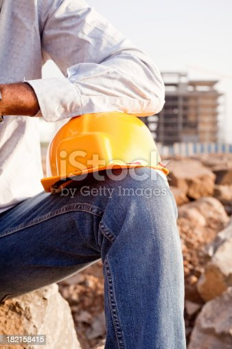 1047558948istockphoto Indian Manual Worker Engineer Holding a Safety Helmet 182158415