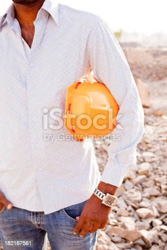 1047558948istockphoto Indian Manual Worker Engineer Holding a Safety Helmet 182167561