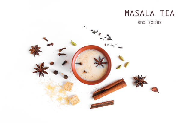 Indian Masala Chai Tea Traditional indian Masala Chai Tea in ceramic cup with ingredients. Spicy black tea with milk isolated on white background, top view, copy space. allspice stock pictures, royalty-free photos & images