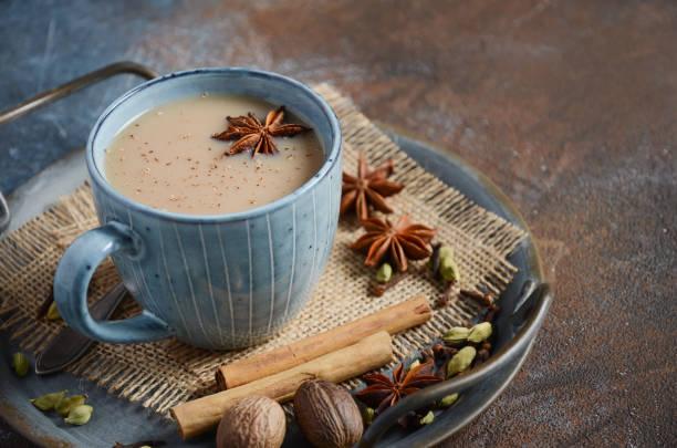 Indian masala chai tea. Spiced tea with milk on dark rusty background. stock photo