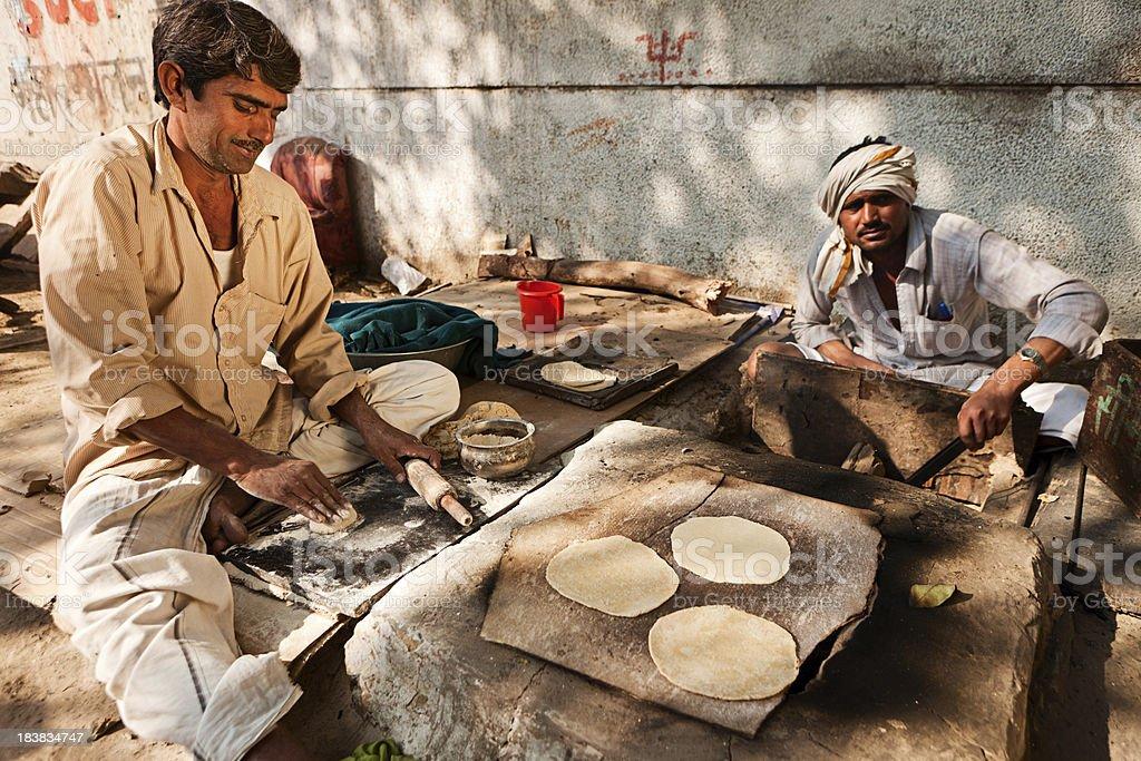 Indian men preparing chapatti bread in Delhi royalty-free stock photo