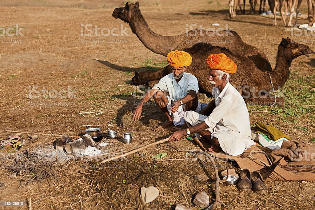 Indian men sitting next to the fireplace during Pushkar festival. stock photo